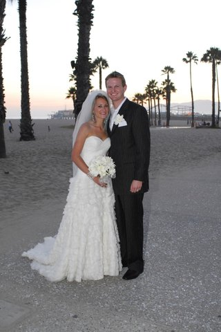 bride-and-groom-stand-on-santa-monica-beach
