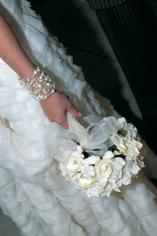 bride-wearing-bracelet-holds-white-flower-bouquet