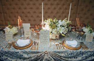 table-with-blue-tablecloth-gold-place-settings-and-white-flowers