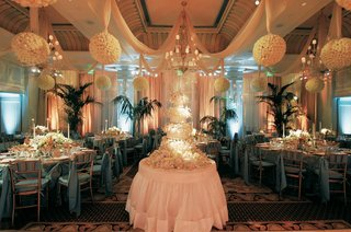 indoor-reception-decorated-with-hanging-ivory-balls-and-blue-linens