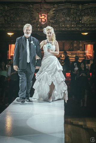 bride-walking-down-catwalk-at-theater-with-father-of-bride