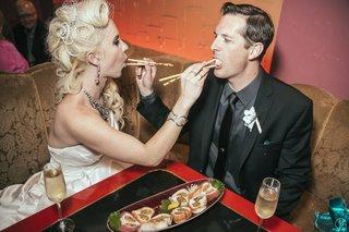 bride-and-groom-feeding-each-other-sushi-rolls