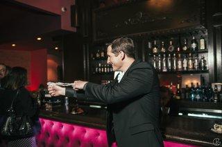 groom-flinging-leg-garter-in-front-of-theater-bar-area