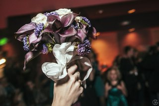 bride-holding-up-white-and-purple-wedding-flowers
