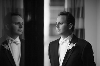 black-and-white-photo-of-groom-looking-at-reflection