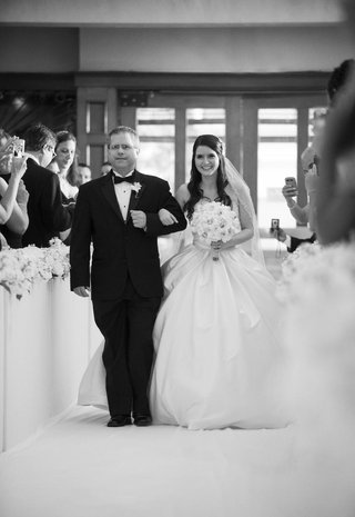 black-and-white-photo-of-bride-walking-down-aisle-with-father