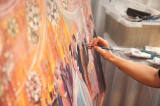 artist-painting-scene-of-wedding-reception-on-canvas