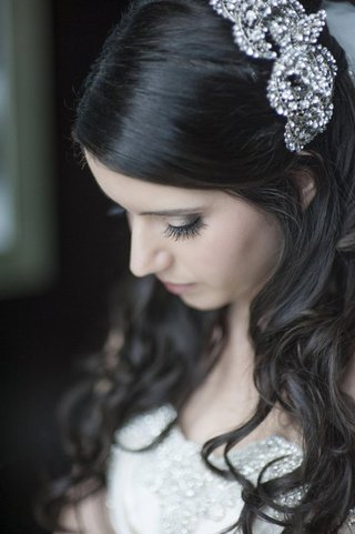 bride-with-brown-hair-looks-down-with-crystal-headband