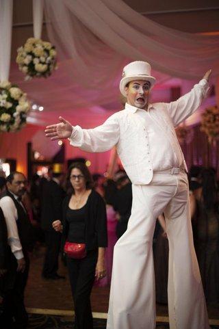 man-in-white-top-hat-on-stilts-at-wedding-reception