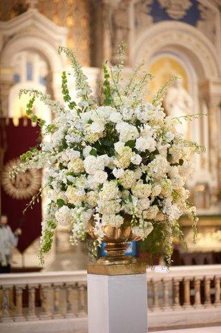 white-flowers-in-gold-urn-vase-at-catholic-ceremony
