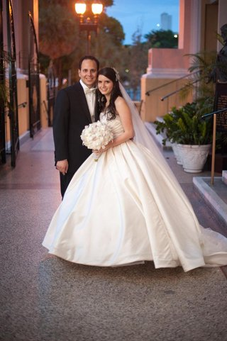 bride-in-ball-gown-and-groom-smile-in-florida