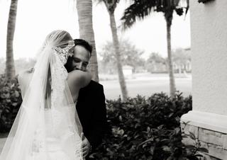 black-and-white-photo-of-bride-hugging-groom-in-veil