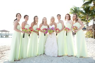 bridesmaids-in-long-dresses-and-flip-flops-with-bride