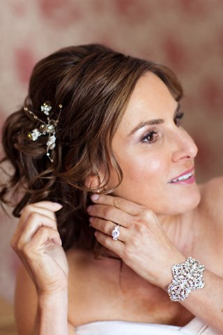 bride-wears-floral-hairpin-and-a-rhinestone-and-pearl-cuff-bracelet
