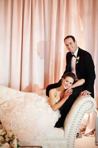 bride-and-groom-relax-on-chaise-at-reception