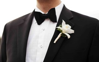groomsman-in-tuxedo-and-bow-tie-with-white-boutonniere