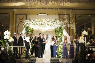 bride-and-groom-under-white-and-green-chuppah
