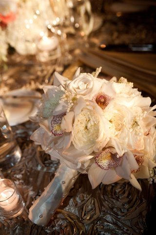 wedding-bouquet-with-rose-and-orchid-flowers-on-reception-table