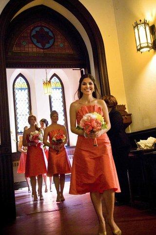 bridesmaids-in-short-dresses-walk-down-church-aisle