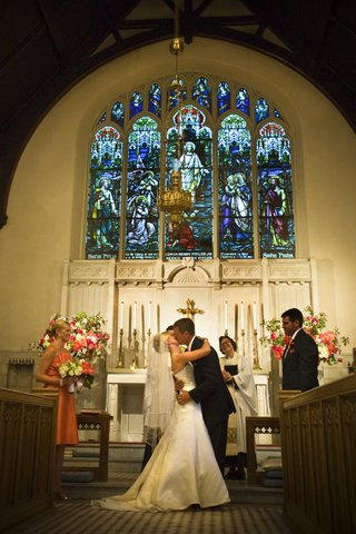 bride-and-groom-kiss-at-church-altar-in-wedding