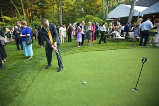 male-guest-putts-golf-ball-during-outdoor-cocktail-hour