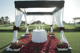 black-and-white-ceremony-structure-with-red-rose-petals-on-golf-course