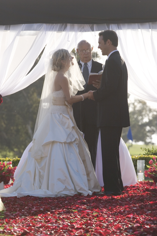 bride-and-groom-stand-on-red-flower-petals-at-altar-with-officiant