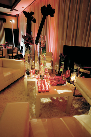 conversation-area-with-white-couches-and-large-red-flower-arrangements