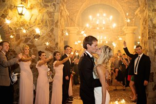 bride-in-a-strapless-romona-keveza-gown-kisses-groom-surrounded-by-guests-holding-sparklers
