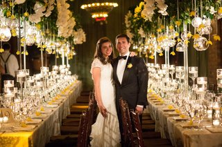 bride-in-lace-cap-sleeve-wedding-dress-mark-ingram-atelier-in-reception-room-yellow-decorations
