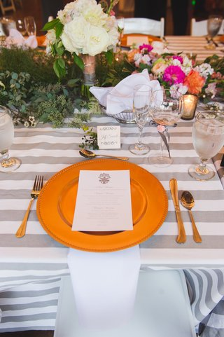 gold-charger-on-gray-striped-tablecloth-with-floral-runner