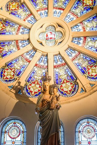 statue-and-stained-glass-window-in-circle-shape-at-chicago-church-ceremony