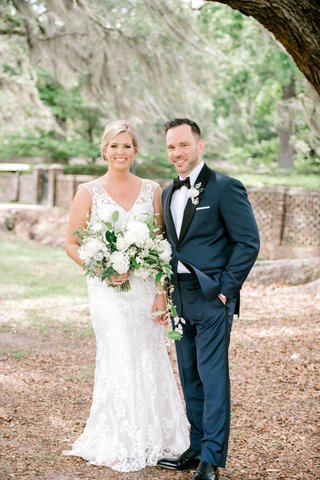 bride-in-v-neck-embroidered-wedding-dress-sleeveless-groom-in-navy-blue-suit-black-lapel-tuxedo-tie