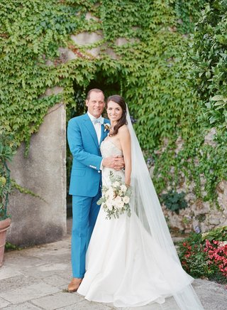 bride-in-strapless-gown-and-groom-in-blue-suit-and-brown-shoes-bow-tie-italy-wedding