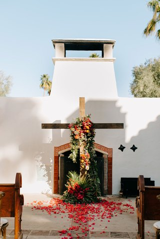 wedding ceremony outdoor courtyard la quinta resort and club wood cross pink flowers tropical greenery