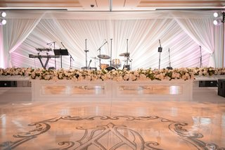 wedding reception large white dance floor with monogram mirror stage white flowers drapery
