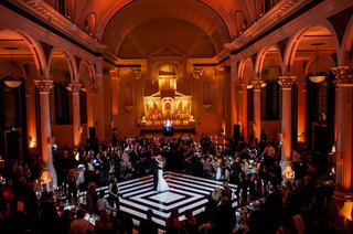 red-orange-lighting-at-vibiana-as-bride-and-groom-dance-on-white-and-black-dance-floor-diamond