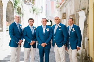 groom-in-blue-suit-with-bow-tie-groomsmen-in-blue-jacket-khaki-pants-and-blue-ties-boutonniere-italy