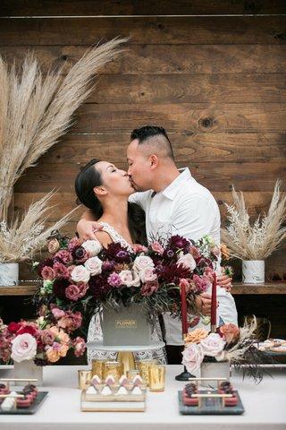 bride-and-groom-kissing-at-bridal-shower-after-groom-delivers-flowers