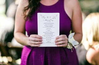 guest-holds-white-wedding-ceremony-program-with-banner-monogram-and-pink-hummingbirds