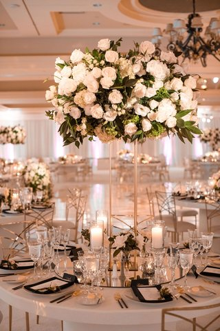 wedding reception round white table mirror base gold stand white rose hydrangea greenery flower arrangement