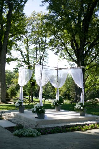 chuppa-chuppah-with-white-sheer-fabric-and-potted-white-flowers-at-outdoor-ceremony