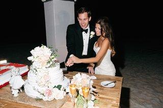 bride-in-a-strapless-anna-maier-ulla-maija-gown-groom-in-black-tuxedo-cut-white-wedding-cake