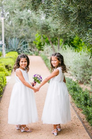 flower-girls-in-white-dresses-with-pink-and-purple-bouquets-hold-hands-in-arizona