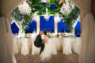 bride-and-groom-at-head-table-vow-renewal-kiss-as-sun-goes-down-chandeliers-overhead-candlelight
