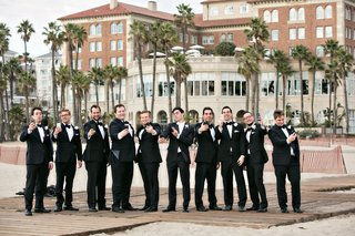 groomsmen-taking-self-portraits-on-their-phones-selfie-photo-on-beach-boardwalk-in-santa-monic
