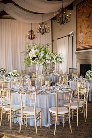 gold-chiavari-chairs-lucite-vessel-holding-green-and-white-flower-arrangement