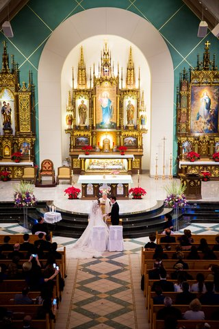 wedding-ceremony-bride-and-groom-at-altar-traditional-wedding-white-chairs-gold-altar-arch-pews