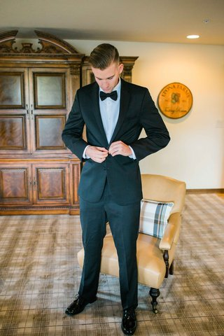 groom-buttons-coat-jacket-of-tuxedo-preparing-for-wedding-ceremony