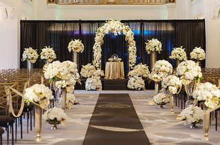 indoor-wedding-with-black-gold-and-ivory-multiple-flower-arrangements
